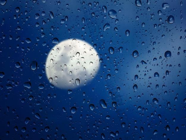 Luna vista a través de un vidrio mojado al atardecer.