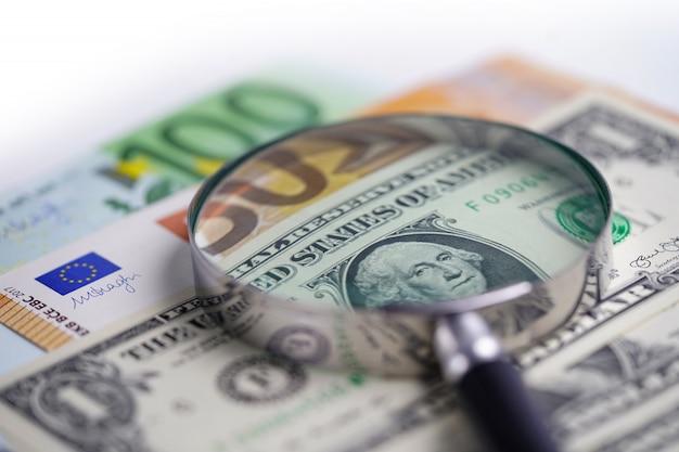 Lupa en billetes de euro y dólar estadounidense.