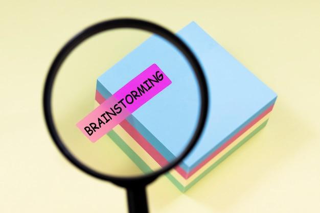 Lupa de cerca con texto brainstorming en pegatina rosa sobre fondo amarillo