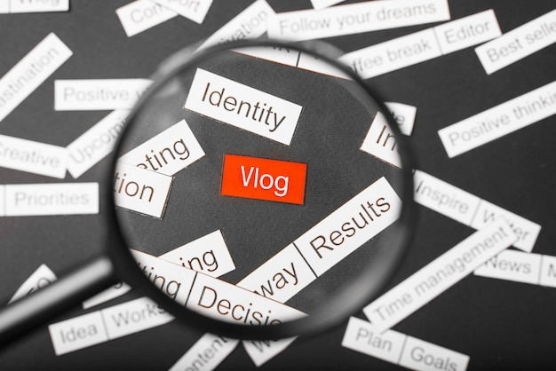 Lupa de cristal sobre el vlog de inscripción rojo cortado de papel. s