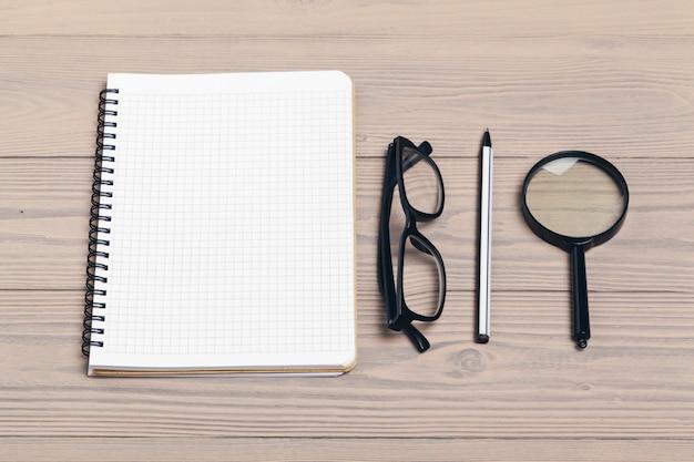 Lupa y cuaderno sobre mesa de madera