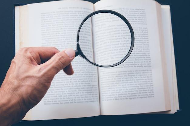 Lupa en mano y libro sobre la mesa