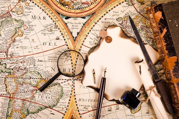 Lupa, papel quemado, pluma y botella de tinta, cuchillo y monedas en el mapa mundial