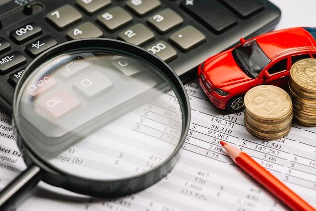 Lupa sobre la calculadora y el informe financiero con pila de coche y monedas