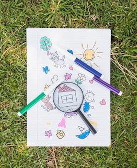 Lupa sobre dibujo infantil sobre hierba.