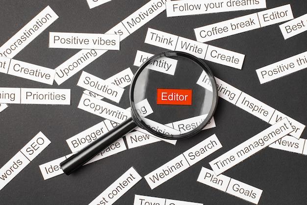 Lupa sobre el editor de inscripción rojo cortado de papel. rodeado de otras inscripciones sobre un fondo oscuro. nube de palabras.