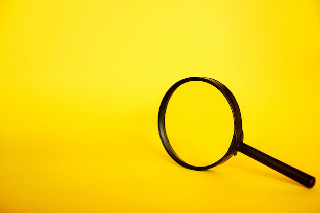 Lupa sobre fondo amarillo. concepto de búsqueda