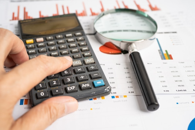 Lupa sobre gráficos papel cuadriculado desarrollo financiero banca