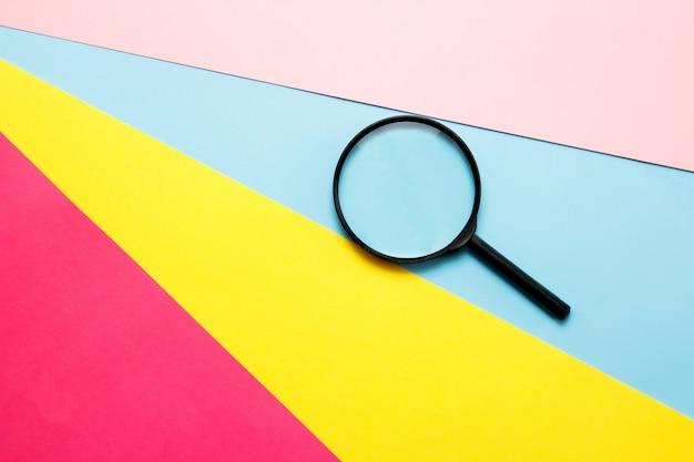 Lupa sobre papel de color. vista superior. concepto de búsqueda