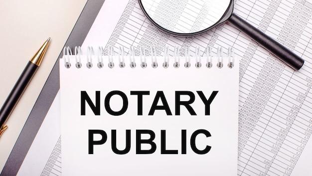 Lupa de sobremesa, informes, bolígrafo y cuaderno con texto notario público. concepto de negocio