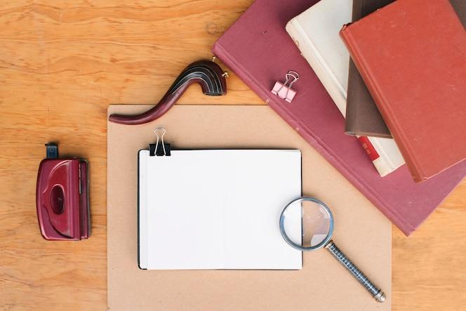 Lupa y tubería cerca de cuadernos