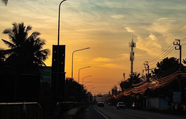 Luz del atardecer detrás de los árboles de coco y la carretera.