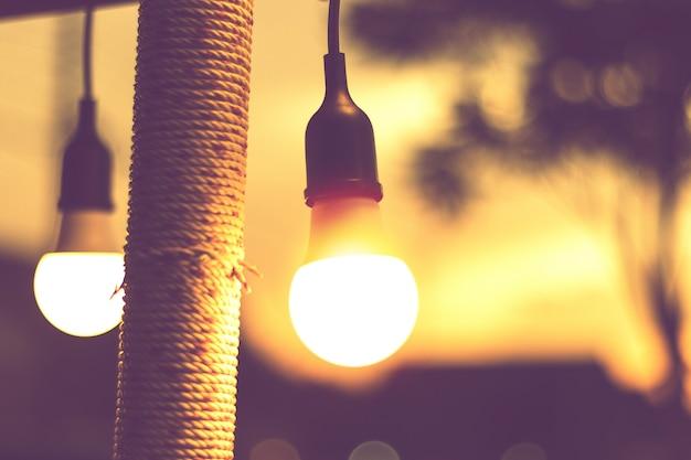 Luz bokeh borrosa en la puesta de sol con decoración de luces de cadena amarilla en restaurante de playa