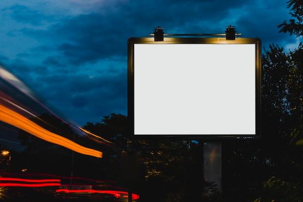 Luz borrosa del rastro cerca de la cartelera en blanco blanca para el anuncio en la noche