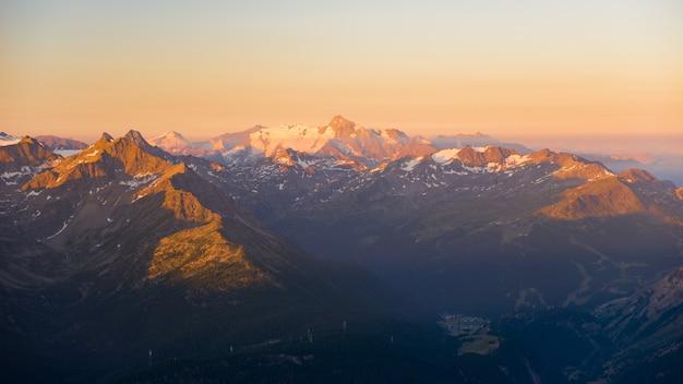Luz cálida al amanecer en picos de montañas, crestas y valles