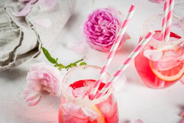 Luz de cóctel rosa rosa, con vino rosado, el té de pétalos de rosa y limón en una mesa de hormigón de piedra blanca.