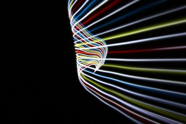 La luz del color del arco iris se mueve en una toma de larga exposición en la oscuridad.