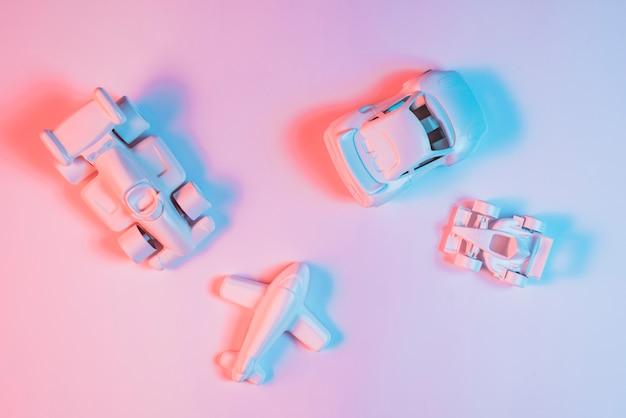Luz de color azul en juguetes de vehículos de transporte sobre fondo rosa