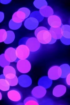 Luz de decoración iluminada abstracta púrpura y rosa borrosa sobre fondo oscuro