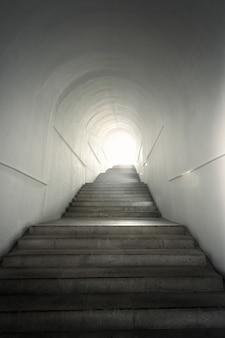 Luz del final del túnel con escaleras ascendentes