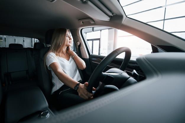 Luz natural. chica en coche moderno en el salón. durante el día en interiores. comprar vehículo nuevo