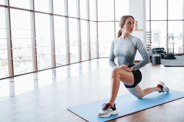 Luz natural. deportiva joven haciendo ejercicios en el gimnasio por la mañana