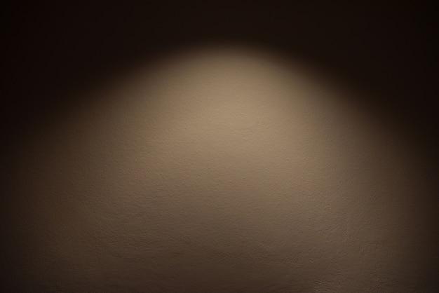 Luz en la pared: la lámpara brilla con luz cálida en la pared marrón / efecto de luz