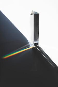 Luz que pasa a través de un prisma triangular con sombra oscura sobre superficie blanca