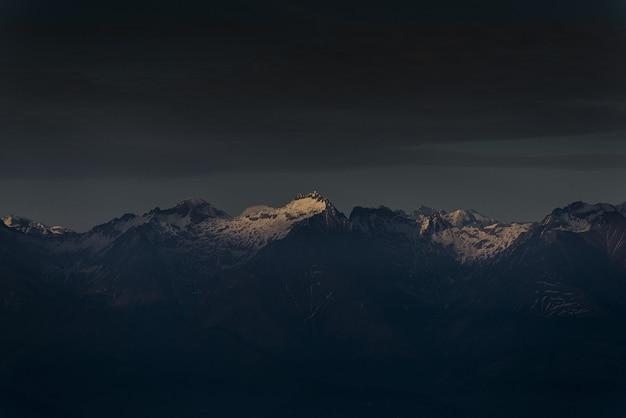 La luz del sol brillando en la cima de una montaña al atardecer con cielo nublado oscuro