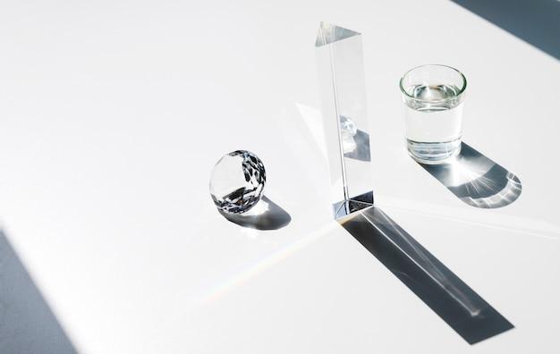 La luz del sol cae sobre el diamante; prisma y vaso de agua con sombra sobre fondo blanco