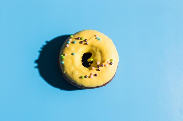 La luz del sol de moda. donut sobre fondo turquesa azul claro brillante. concepto mínimo de verano. estilo pop art