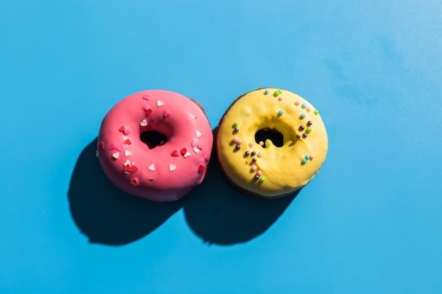 La luz del sol de moda. donuts de verano sobre fondo turquesa azul claro brillante. concepto mínimo de verano. estilo pop art rosquilla