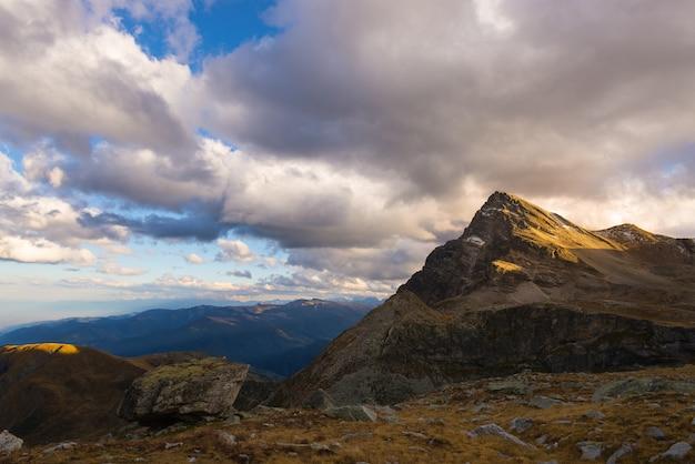 Luz del sol en los picos de las montañas del valle alpino y nubes escénicas
