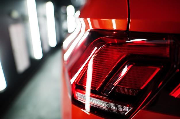 Luz trasera de un bonito y nuevo coche deportivo de color naranja en un garaje moderno.