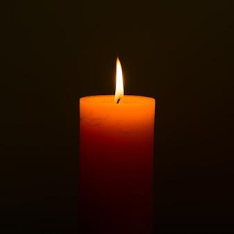 Luz de vela con llama sobre fondo negro