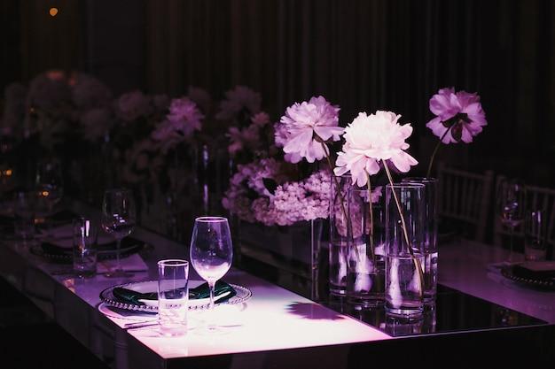 Luz violeta sobre la mesa puesta con flores.