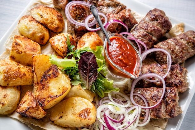 Lyulya kebab con salsa roja, cebolla y papas en plato blanco de cerca