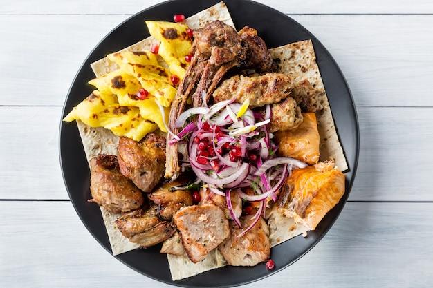 Lyulya kebab, shish kebab, salmón a la plancha, cebolla y granos de granada en plato negro y mesa de madera blanca