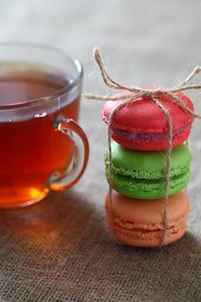 Macaron tres piezas rojas, verdes y naranjas atadas con una cuerda y una taza con té sobre mantel de arpillera. marco vertical