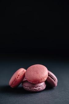 Macarones rosas sobre fondo oscuro