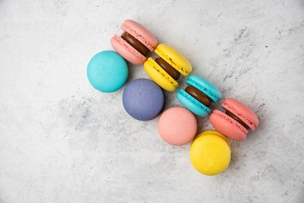 Macarons de almendras de colores sobre fondo blanco. vista superior.