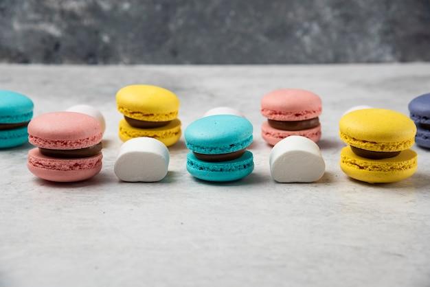 Macarons de almendras de colores sobre mesa blanca con malvaviscos.