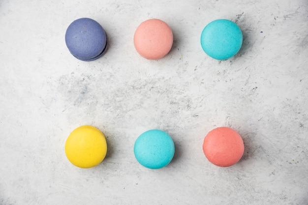 Macarons de almendras de colores sobre superficie blanca. endecha plana.