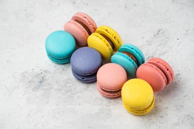 Macarons de almendras de colores sobre superficie blanca. vista superior.