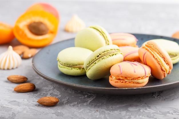 Los macarons anaranjados y verdes o los macarrones se apelmazan en la placa de cerámica azul en un fondo gris del hormigón. vista lateral, enfoque selectivo.