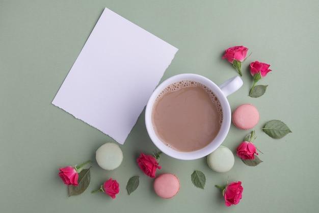 Macarons, café y rosa sobre fondo verde. vista superior. endecha plana