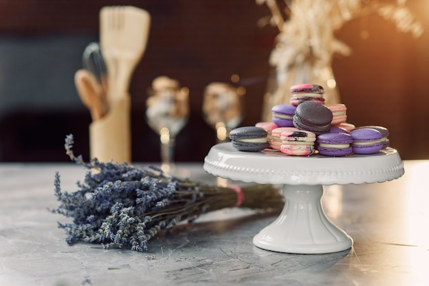 Macarons de colores en una bandeja blanca sobre una mesa de mármol con una servilleta, lavanda y accesorios de cocina.