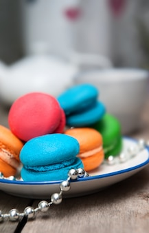Macarons de colores en plato blanco sobre mesa de madera.