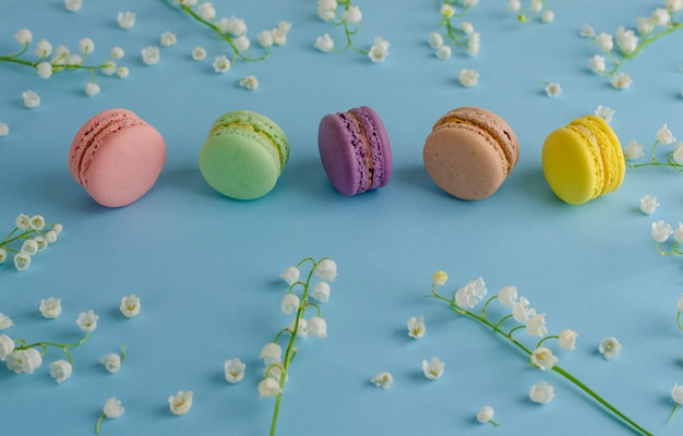 Macarons coloridos o macarrones decorados con flores florecientes de lirio de los valles en azul pastel. dulce concepto de postre francés. vista superior. copyspace