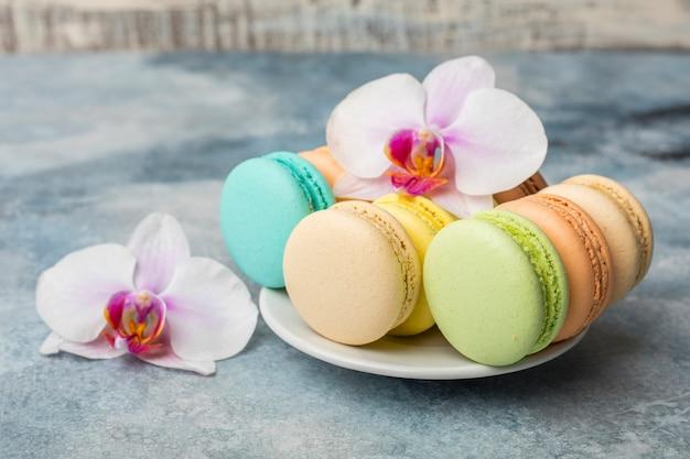 Macarons coloridos en un plato en azul
